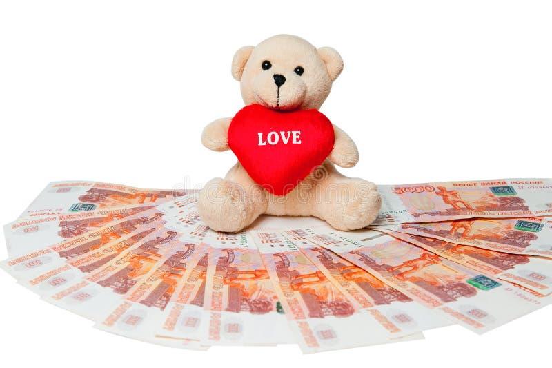 Geld Teddybär, der auf dem Geld sitzt Geld aus verschiedenen Ländern stockfoto