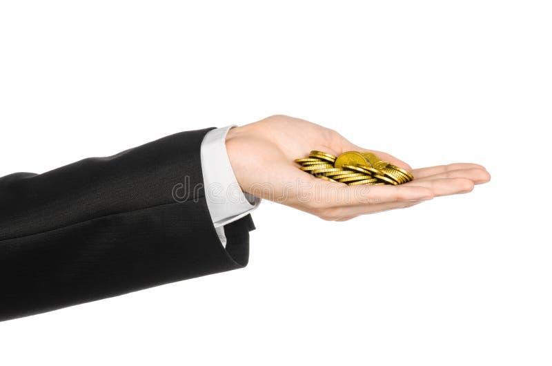 Geld und Geschäftsthema: übergeben Sie in einem schwarzen Anzug, der einen Stapel von Goldmünzen im Studio auf einem weißen Hinte lizenzfreie stockfotografie