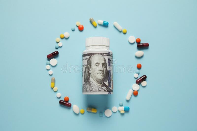Geld und Tabletten in verschiedenen Farben auf blauem Hintergrund Steigende Kosten im Gesundheitswesen stockfotos