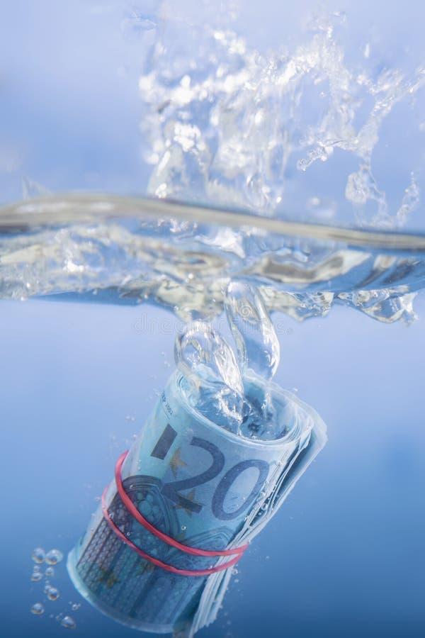 Geld und Wirtschaftskonzept Zeigen der Eurobanknote, die in Wasser als Symbol der globalen Wirtschaftskrise in Europa sinkt lizenzfreie stockfotos