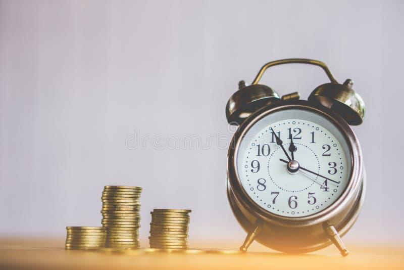 Geld und Zeitkonzept mit Stapel der Münze und der Uhr auf Tabelle lizenzfreie stockfotos