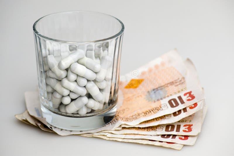 Geld unter Glas der Pille stockbilder