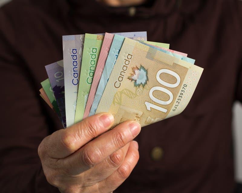 Geld van Canada: Canadese Dollars Oude teruggetrokken persoon die in contant geld betalen stock foto's