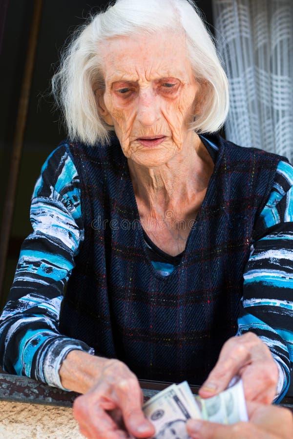 Geld van de oma het tellende pensionering thuis stock fotografie