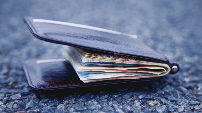 Geldbörse mit Geld auf der Straße Vergeudetes Zeit ist Geld verlorenes Konzept stockfotografie