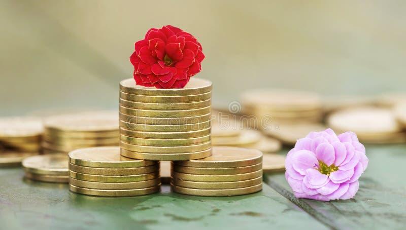 Geldbesparingen in de lente - gouden muntstukken en bloemen stock foto's