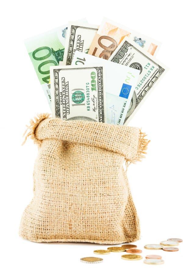 Gelddollars en euro in de dichtbij verspreide linnenzak en de muntstukken royalty-vrije stock foto's