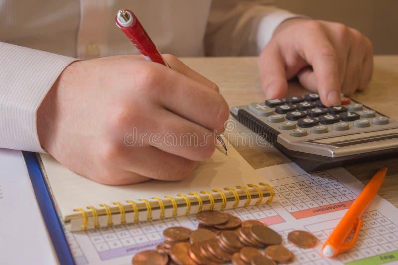 Geldmünzen, Taschenrechner und einige Schreibwaren auf Holztisch - finanzieller Hintergrund stockbild