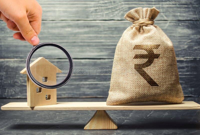 Geldtasche mit Rupie der indischen Rupie und Holzhaus auf Skalen Angemessener Wert von Immobilien und von Wohnung Zahlung der Hyp stockbilder