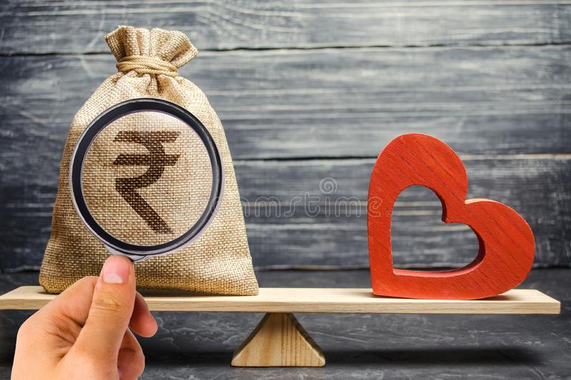 Geldtasche mit Rupie der indischen Rupie und rotes hölzernes Herz auf den Skalen Geld gegen Liebeskonzept Familie oder Berufswahl stockfotos