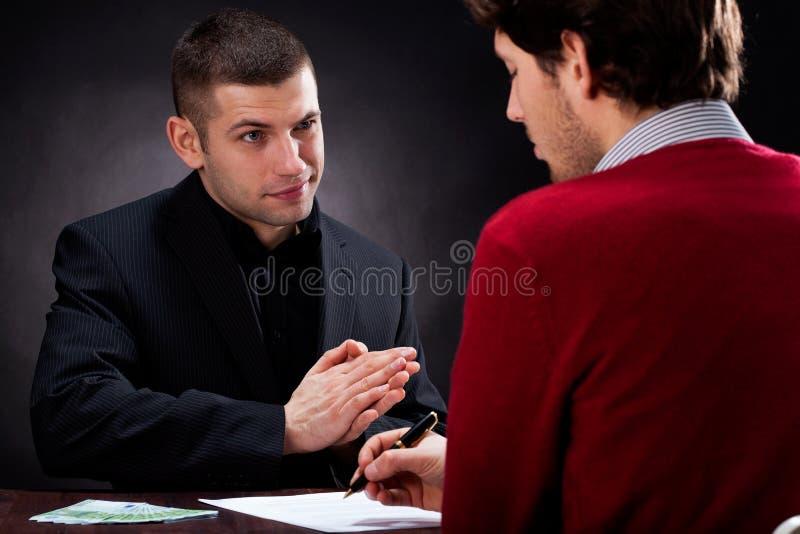 Geldverleiher, der mit Kunden spricht stockbilder