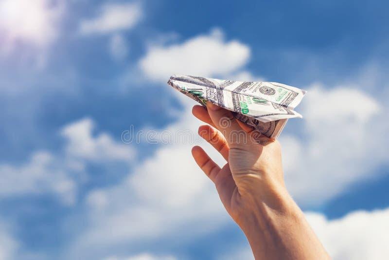 Geldvliegtuig op de vingers over hemel met wolken royalty-vrije stock afbeelding