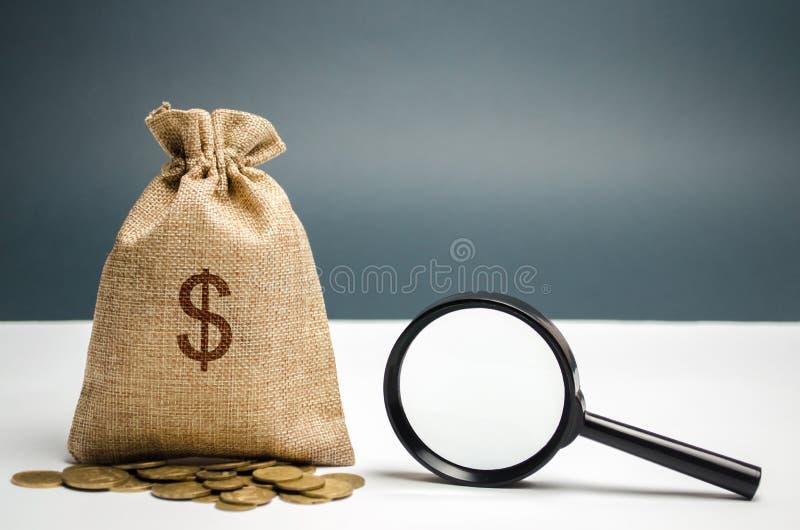 Geldzak met dollarteken en vergrootglas Het concept het vinden van bronnen van investering en sponsors Liefdadige fondsen stock foto's