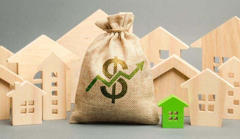 Geldzak met pijl omhoog en miniatuurblokhuizen Het concept toenemende bezitsprijzen Hoge hypotheektarieven Dure huur royalty-vrije stock foto's