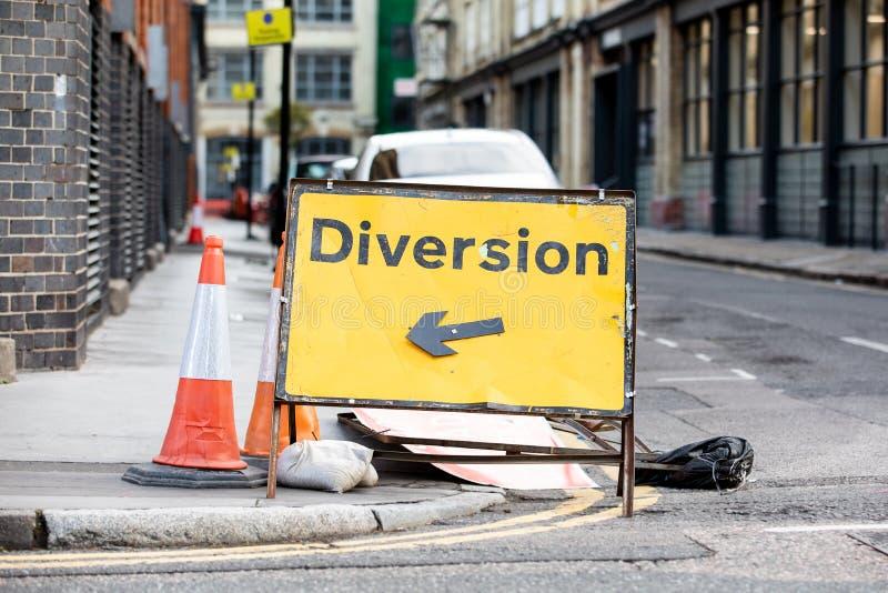 Gele afleidingsactieverkeersteken in een Britse stadsstraat stock foto's