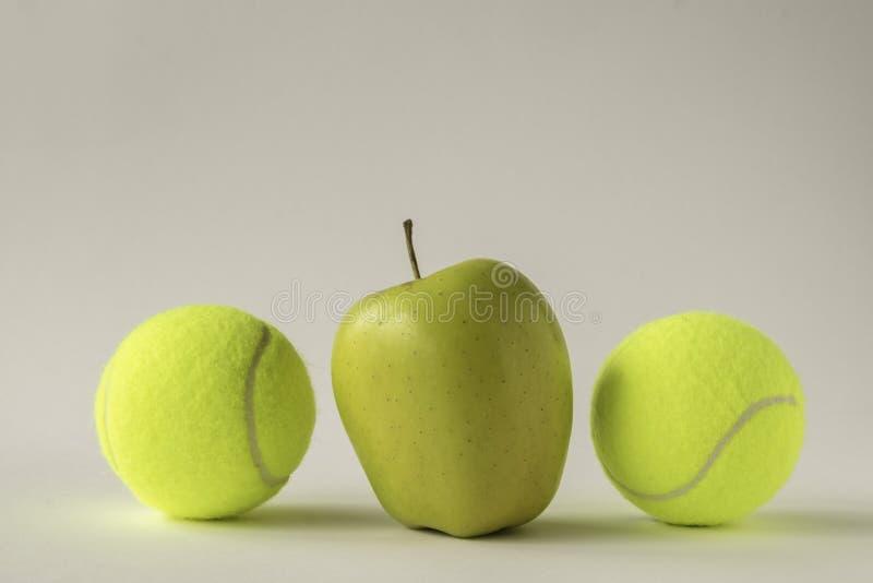Gele appel tussen twee tennisballen stock foto's