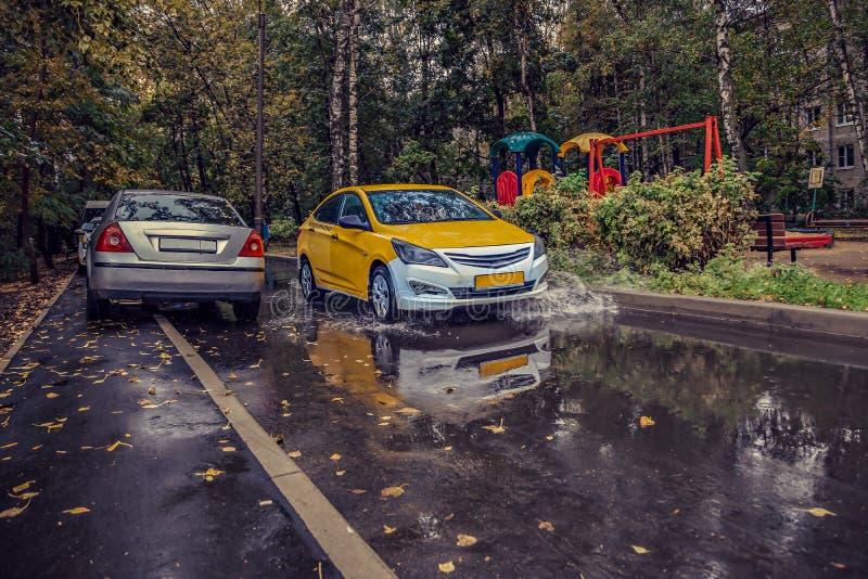 Gele autoritten in de werf op een natte weg in de regen Mooie plonsen van water van onder de wielen stock afbeeldingen