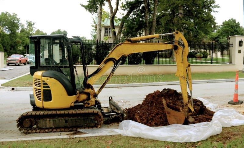 Gele Backhoe met een stapel van vuil op plastiek parkeerde op een buurtstraat voor de betere inkomstklasse met aardig huis een om royalty-vrije stock afbeeldingen