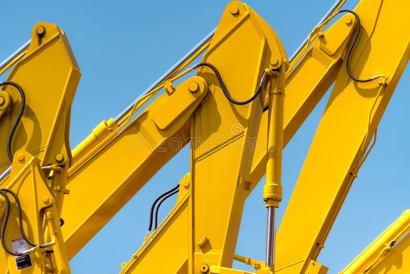 Gele backhoe met hydraulisch zuigerwapen tegen duidelijke blauwe hemel Zware machine voor uitgraving in bouwwerf hydraulisch royalty-vrije stock foto