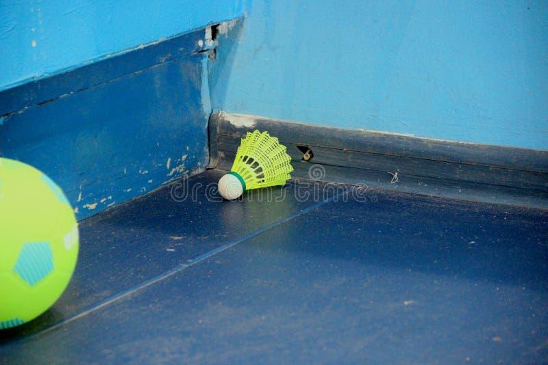 Gele badmintonshuttle op de blauwe vloer in de hoek van de gymnastiek en de gele minivoetbalbal stock afbeeldingen