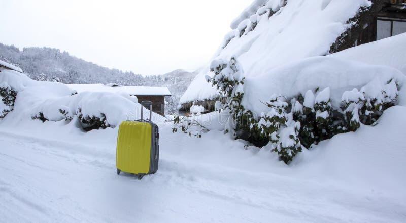 Gele bagage op de weg met sneeuw als achtergrond stock foto's