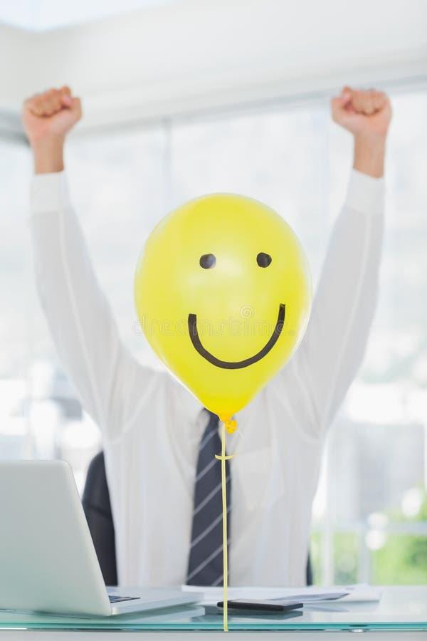 Gele ballon met gelukkig gezicht die vrolijk businessmansgezicht verbergen royalty-vrije stock afbeelding