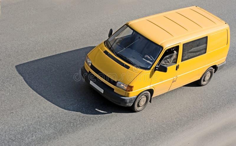 Gele bestelwagen op weg stock foto