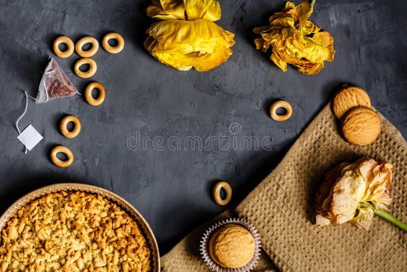 Gele bloem, koekjes en appeltaart die op grijze achtergrond liggen Vlak leg Hoogste mening stock afbeelding