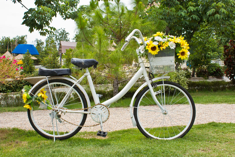 Gele bloem op een decoratieve oude witte geschilderde fiets royalty-vrije stock afbeeldingen