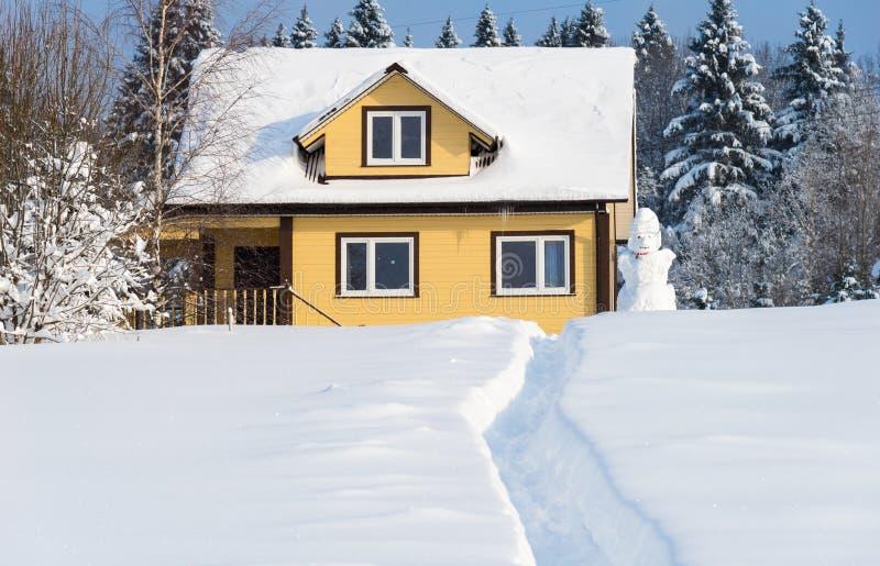 Gele blokhuis en sneeuwman op bosachtergrond in de winter zonnige dag stock afbeeldingen