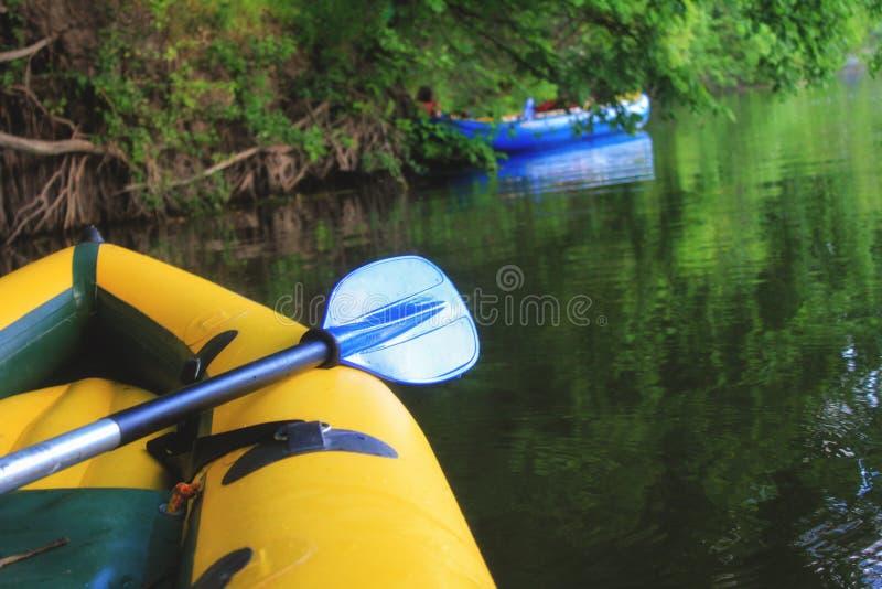 Gele bootneus en blauwe peddel op de nog wateren van de Rivier van Donau royalty-vrije stock fotografie