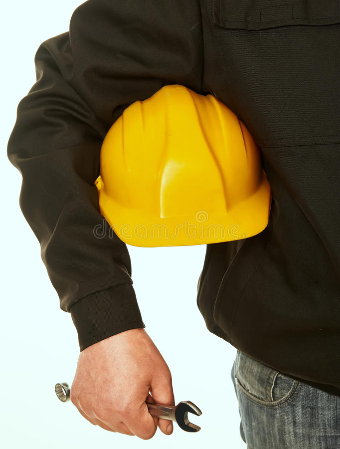 Gele bouwvakker en moersleutel in hand werkende mens stock afbeeldingen