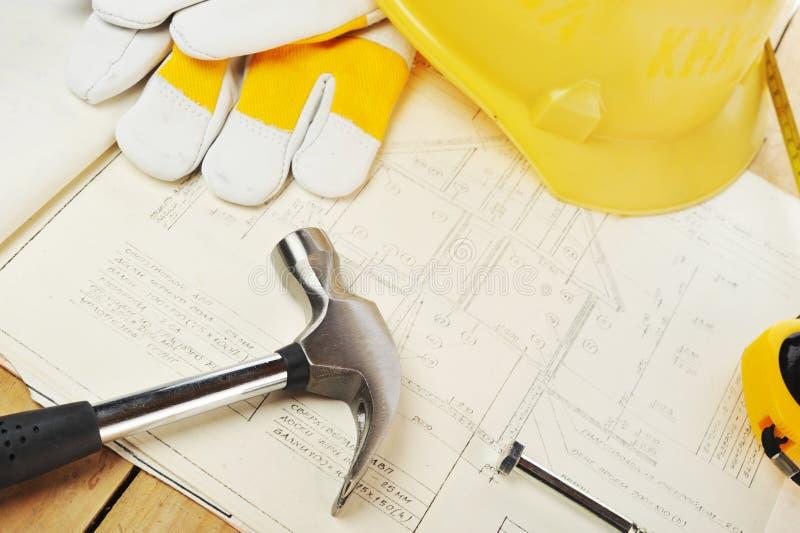 Gele bouwvakker op tekeningen stock foto