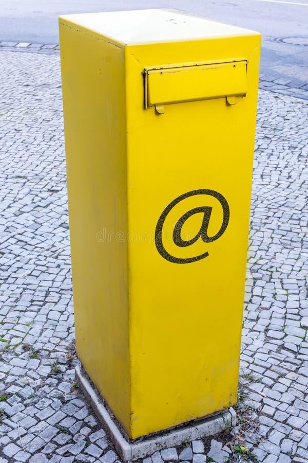 Gele brievenbus met e-mailteken als symbool voor de e-mailpostbus royalty-vrije stock foto's