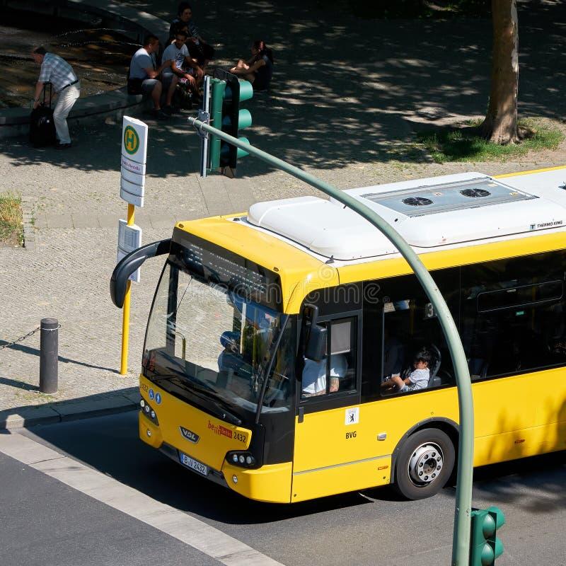 Gele bus bij een bushalte in Berlijn royalty-vrije stock fotografie