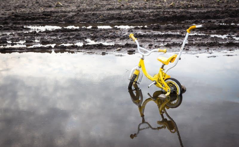 Gele Childs-fietszitting in water op een gebied royalty-vrije stock fotografie