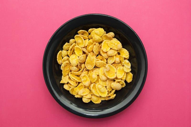 Gele cornflakes in een zwarte plaat op een roze achtergrond royalty-vrije stock foto's