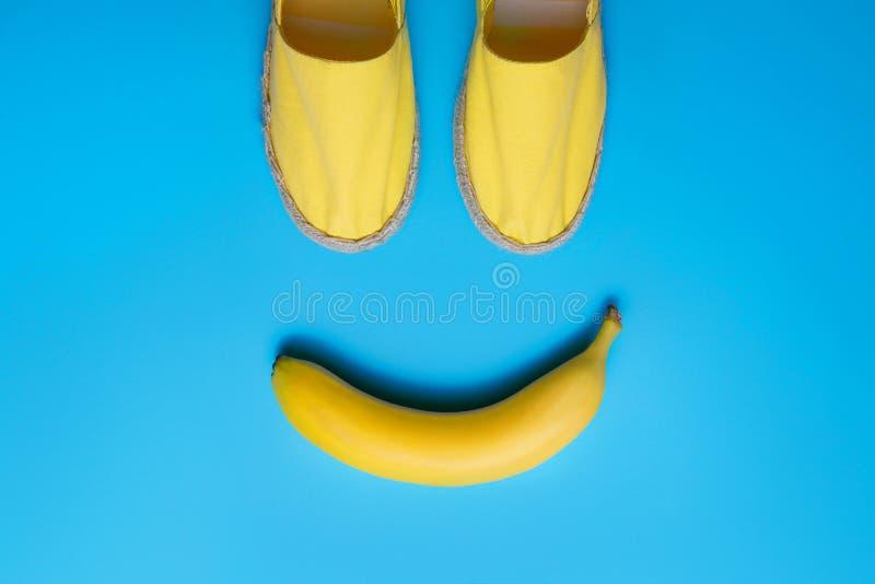 Gele de zomerschoenen en banaan op de blauwe achtergrond Het concept van glimlachemoji stock foto's