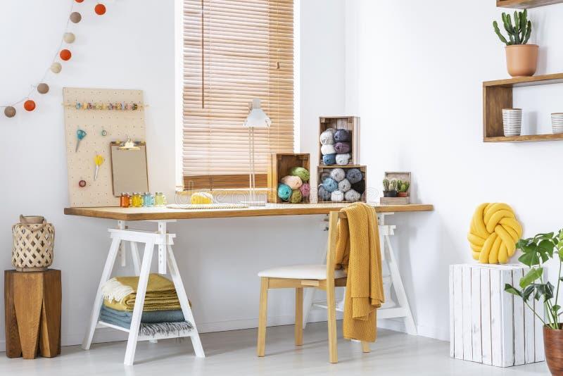 Gele deken op stoel bij houten bureau met lamp en kleurrijke garens in modern binnenland Echte foto stock afbeeldingen