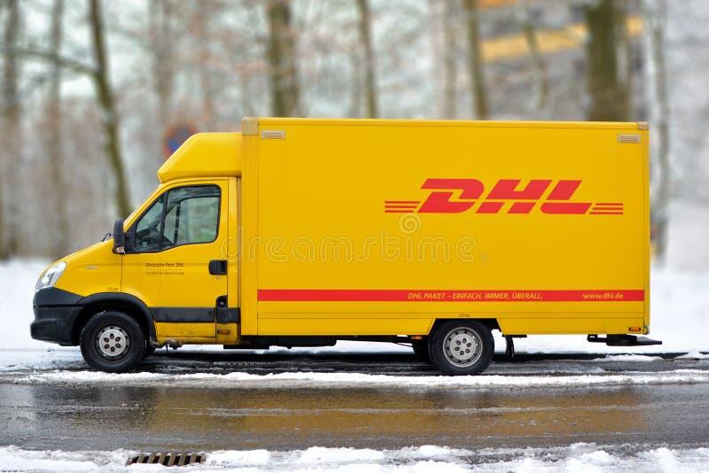 Gele DHL internationale koerier en de dienstvrachtwagen van pakketdeliivery in sneeuw stock fotografie