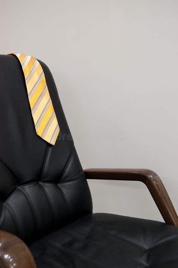 Gele die band over de rug van een zwarte stoel wordt geworpen concept rust vakantieconcept royalty-vrije stock afbeeldingen