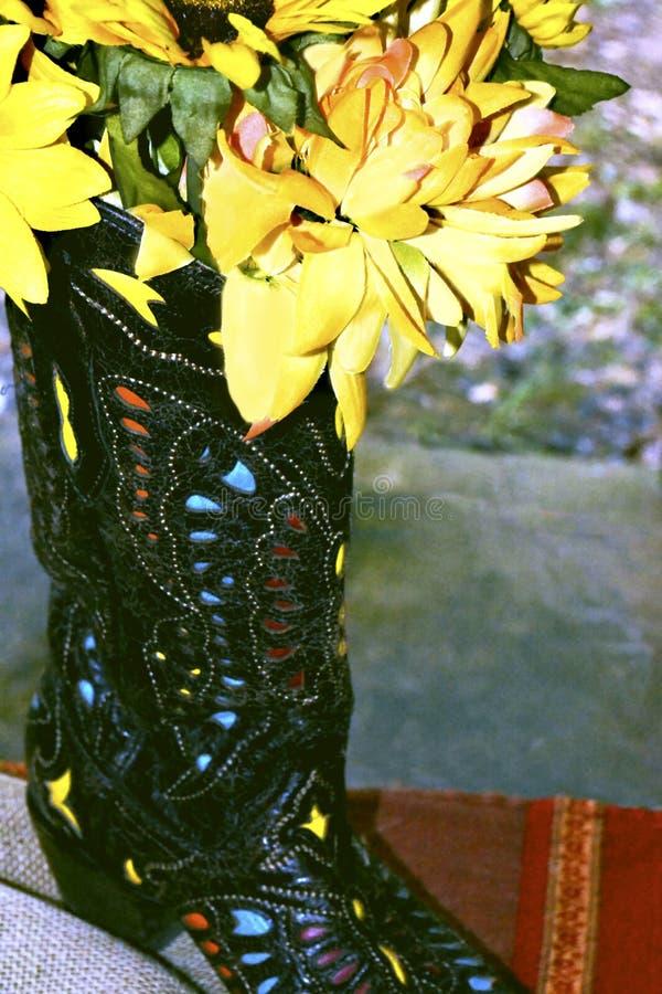 Gele die Bloemen in een Westelijke Laars bij een Rustiek Als thema gehad Huwelijk worden gevuld stock foto