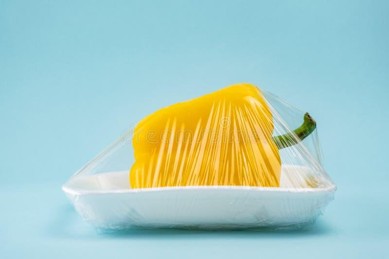 Gele die groene paprika in plastiek clingfilm op blauwe achtergrond wordt verpakt stock foto