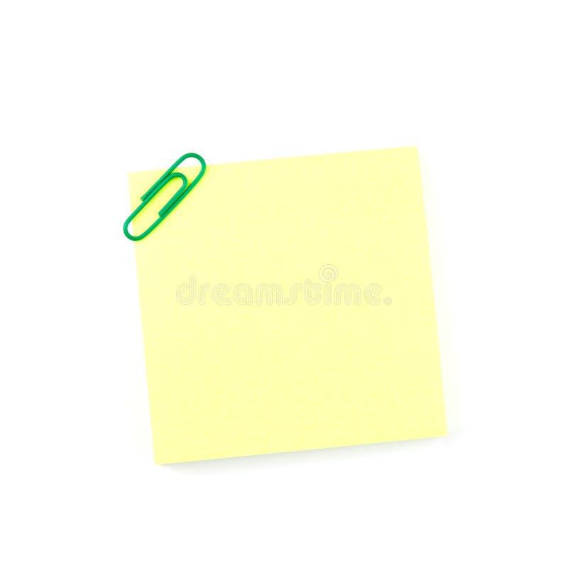 Gele document nota met een groene klem stock afbeeldingen
