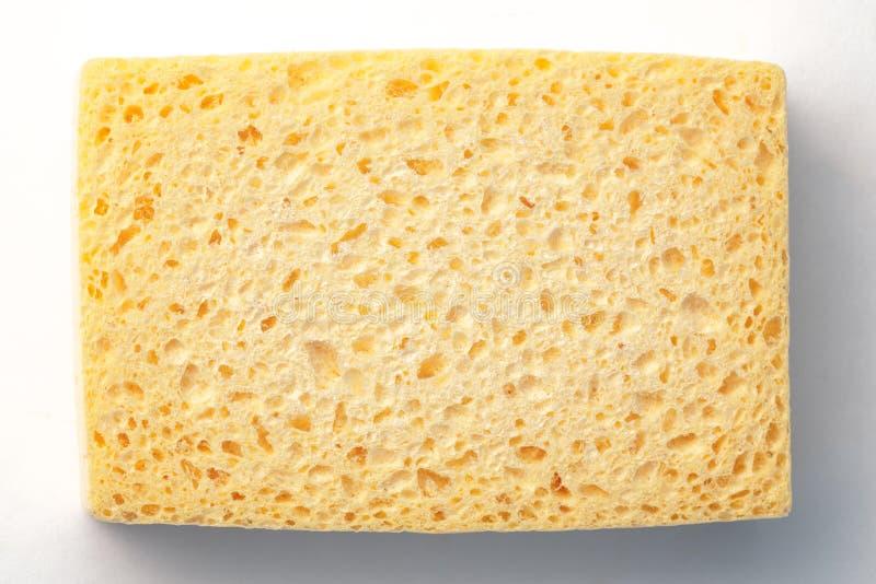 Gele doordrongen spons op witte en grijze achtergrond royalty-vrije stock foto's