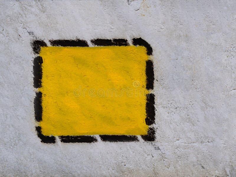 Gele driehoek, vierkant, ruit in zwart gestippeld kader op de oude gemeenschappelijke muur royalty-vrije stock afbeeldingen
