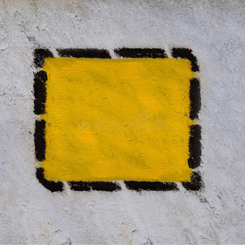 Gele driehoek, vierkant, ruit in zwart gestippeld kader op de oude gemeenschappelijke muur stock foto