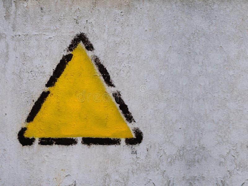 Gele driehoek, vierkant, ruit in zwart gestippeld kader op de oude gemeenschappelijke muur stock foto's