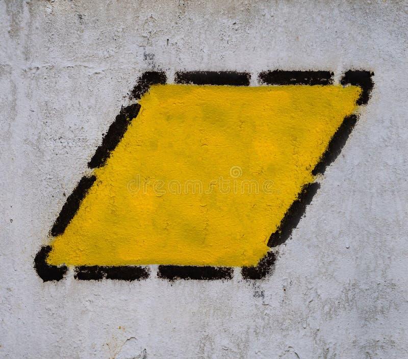 Gele driehoek, vierkant, ruit in zwart gestippeld kader op de oude gemeenschappelijke muur royalty-vrije stock afbeelding