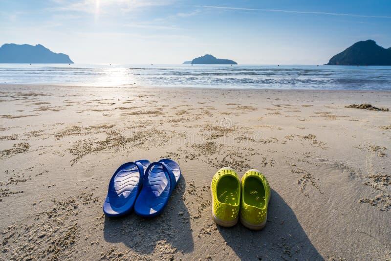 Gele en blauwe schoenen die aan de strandkant worden geplaatst van Ao Manao, ochtend in de zomer, Prachuap Khiri Khan, Thailand stock afbeelding